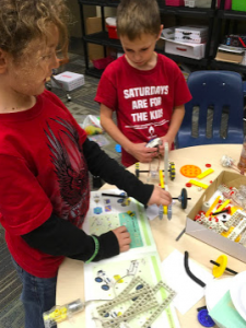 Two students building a remote control machine.