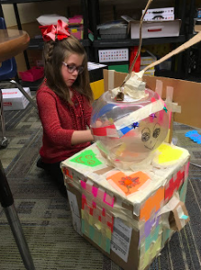 A student building a robot out of makerspace materials.
