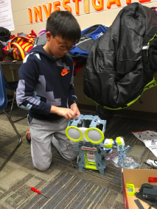 A student putting together a programmable robot.