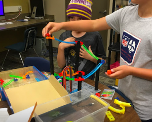 Two students building a roller coaster.